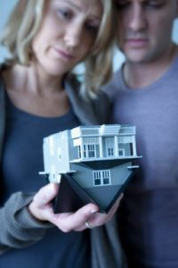 USA, California, Los Angeles, Mid adult couple holding wooden model of house
